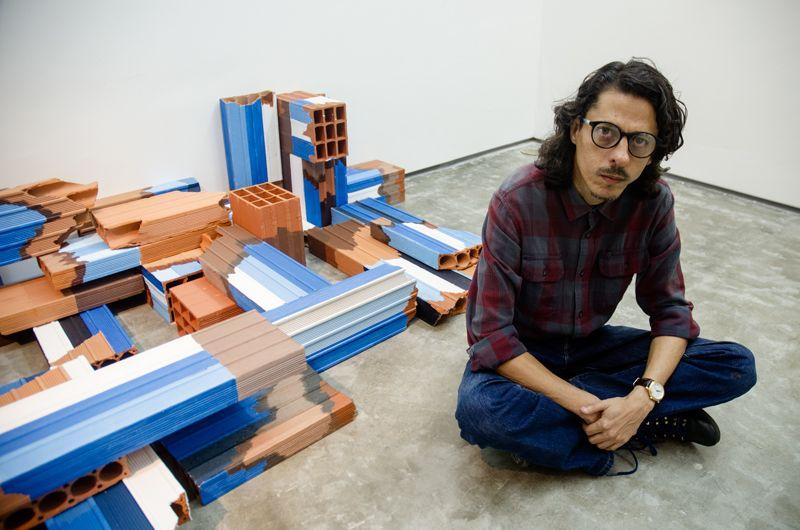 """Alí González junto a su obra """"Acumuladores de sombras"""" Foto: Julio Osorio"""