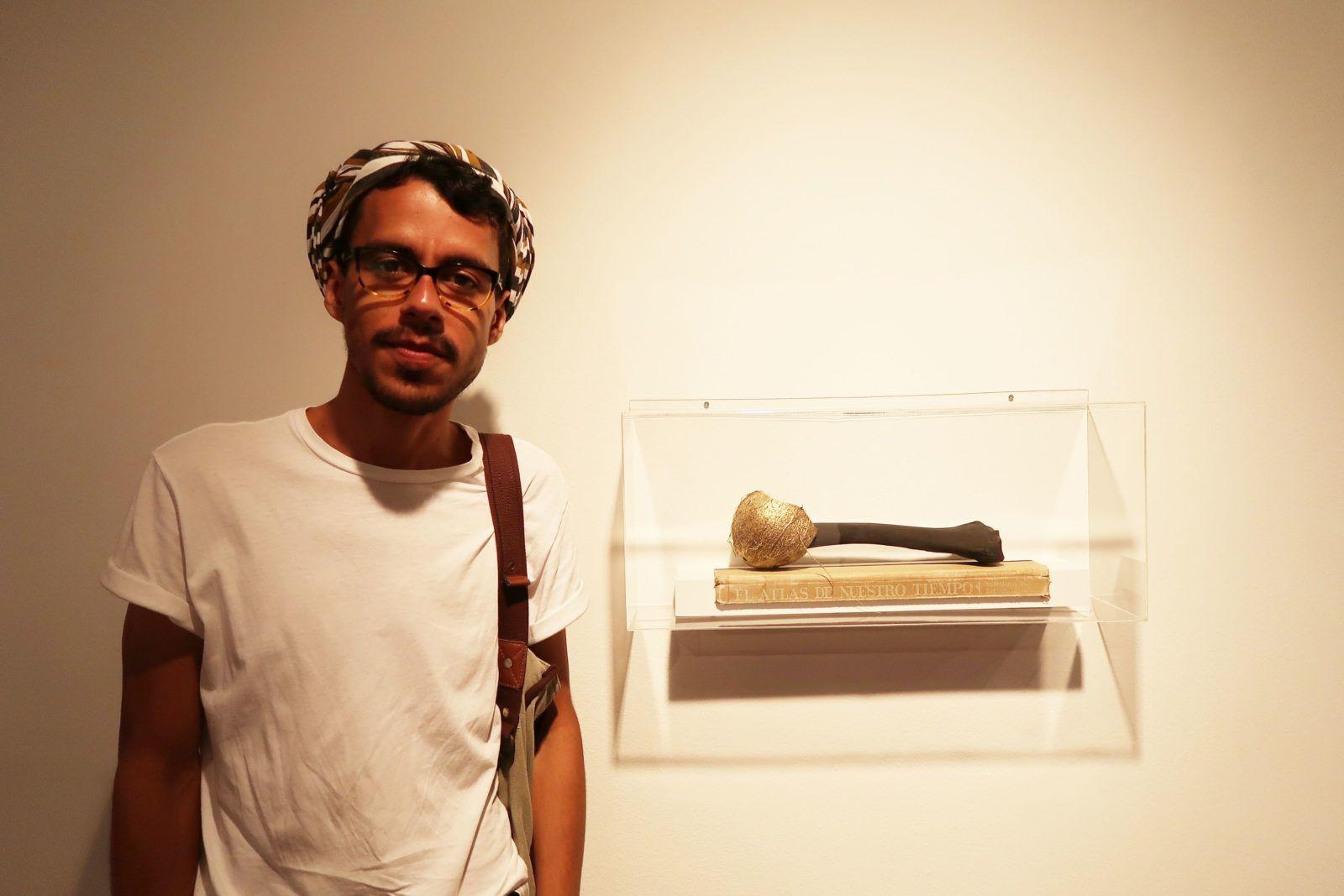 """Eduardo Vargas junto a su obra """"El Atlas de nuestro tiempo"""" de la serie """"Sumario"""" (2016) Foto: Daniela Gustuti"""
